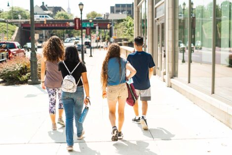 A group of students walk toward a bridge in Downtown Easton.
