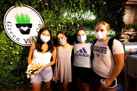 Four students, masked, stand in front of a business in downtown Easton.