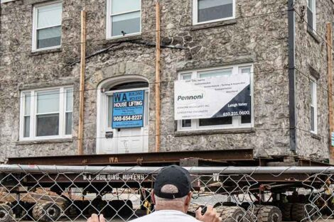 a man looks at the Portlock Black Cultural Center as it's being moved