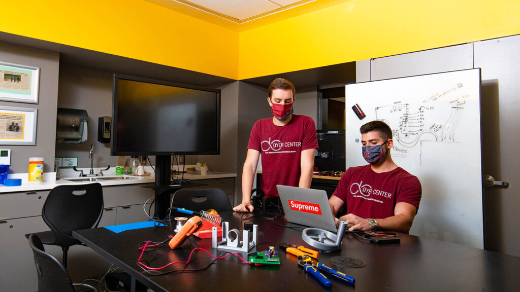 two students work on a laptop wearing masks in Dyer Center Maker Space