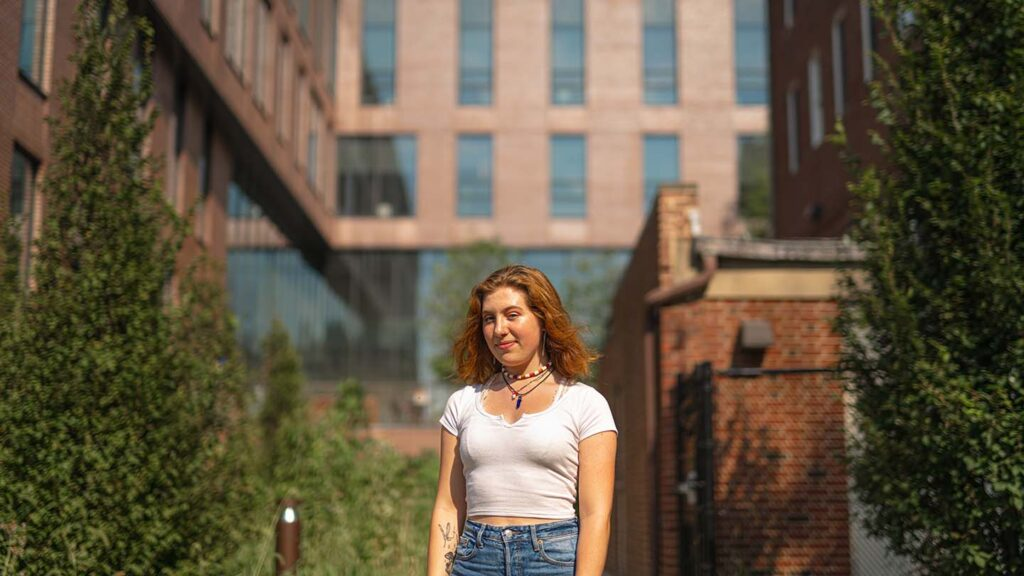 Abigail stands between the buildings at the lower courtyard in Rockwell