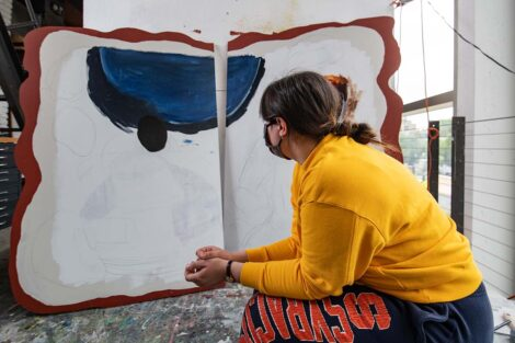 Student contemplates her board with some painted and much still as sketch