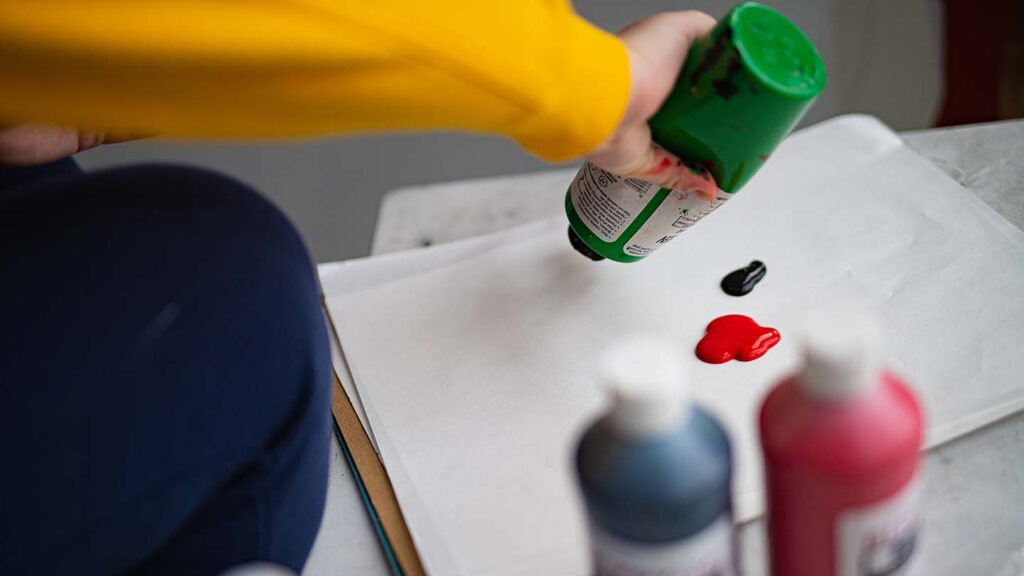 Hand shows a student squeezing out green paint