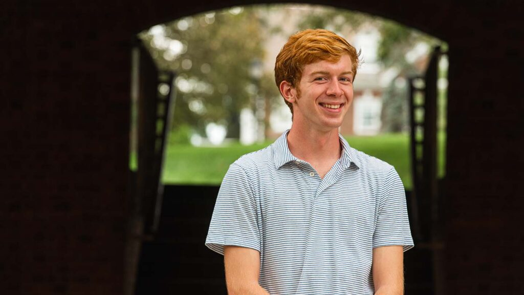 Colin stands under an archway at Ruef Hall