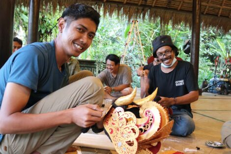 Two men smile as they hold part of a headdress they are creating