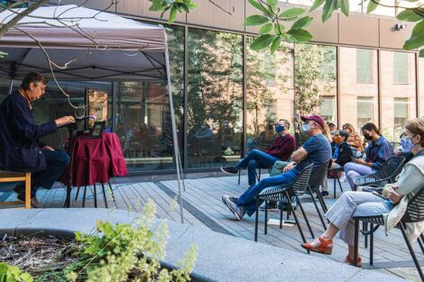 Families sit outside at Goodwyn Plaza, Rockwell Integrated Science Center, listening to John Becica '69