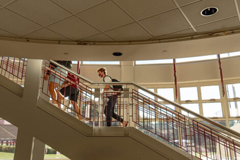 Families, masked, walk up stairs of Kirby Sports Center
