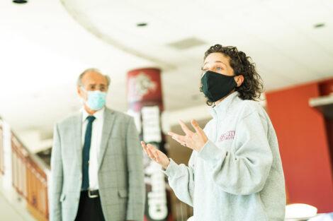 Both wearing masks, Delcia Nahman speaks next to Bruce Ferretti