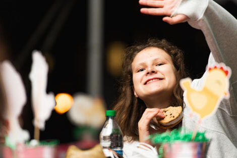 A student waves, holding ice cream while sitting at a table.