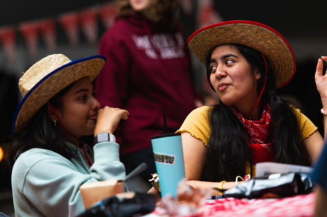 Two students in cowboy hats and bandanas sit at a covered picnic table.