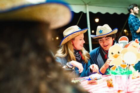 Two students in matching cowboy hats talk at a covered picnic table.