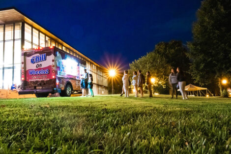 An ice cream truck sits on the Quad outside of Skillman Library, with a line of students.