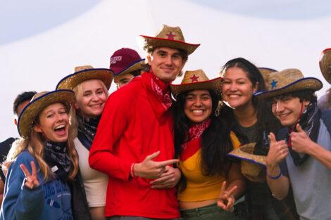 Students smile, wearing cowboy hats and bandanas.