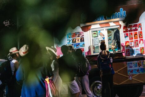 Students stand in line in front of an ice cream truck.