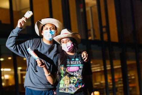 Two masked students hold ice cream bars, wearing matching cowboy hats.