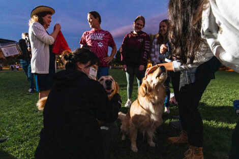 Students and Nicole and Bill Hurd stand around a golden retriever on the Quad