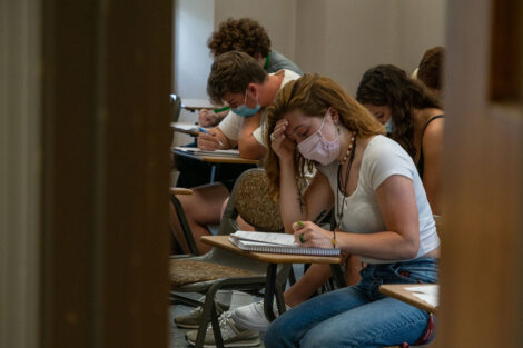 A student, wearing a mask, takes notes in a classroom, surrounded by other students.