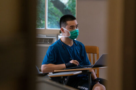 A student, wearing a mask, sits at their desk inside of a classroom at Lafayette College.
