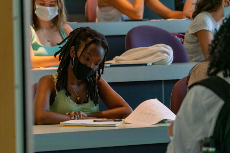 A student, wearing a mask, looks over notes at a desk inside of a classroom.