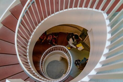 A spiraling staircase. Students, wearing masks and backpacks and carrying books, walk up them.
