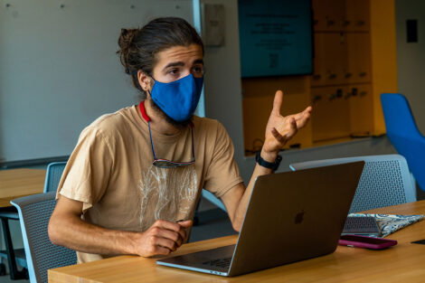 A student, wearing a mask, engages in conversation with their laptop open.