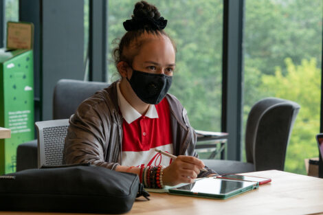 A student, wearing a mask, uses their tablet.