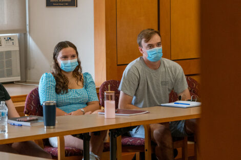 Students, wearing masks, sit in desks inside of a classroom at Lafayette College.