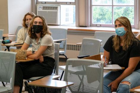Students, wearing masks, sit in desks inside of a classroom.