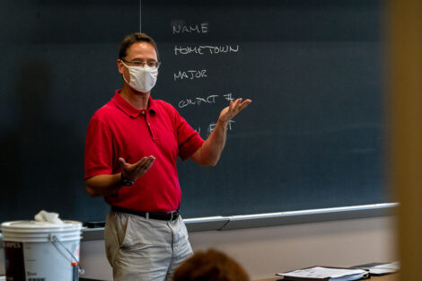 Professor Ethan Berkove, masked, instructs his students in front of a chalkboard.