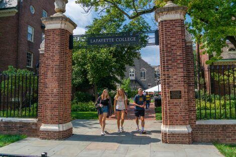 Students walk underneath a brick archway that reads