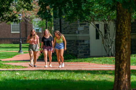 Three students walk along the brick pathway of Lafayette College, engaged in a conversation.