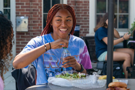 A student smiles as they close their water bottle during lunch.