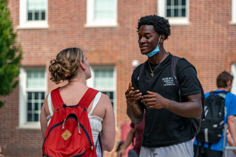 Two students talk outside.