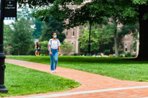 A student, wearing a mask, walks across the brick pathway of Lafayette College's Quad.