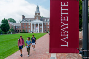 Students walk in front of Watson Hall; a Lafayette College flag hangs on a pole beside the pathway.