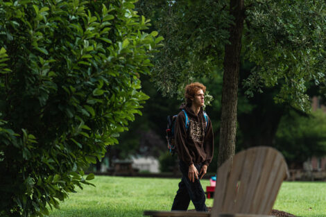 A student walks across Lafayette College's campus, surrounded by greenery.