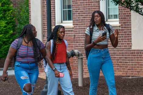 Three students engage in conversation while walking along a brick pathway on Lafayette College's campus.