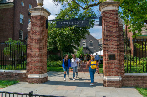 Students walk under an archway that reads