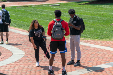 Students talk on the brick pathway outside of Lafayette College's Quad