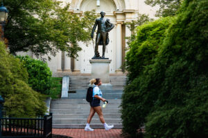A student walks past a statue of Marquis de Lafayette, behind Colton Chapel.