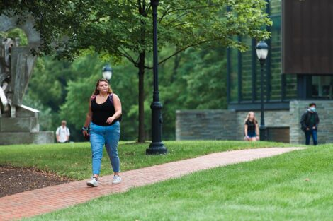 A student walks along a brick pathway in front of Lafayette College's Skillman Library. A portion of the sculpture Transcendence can be seen.
