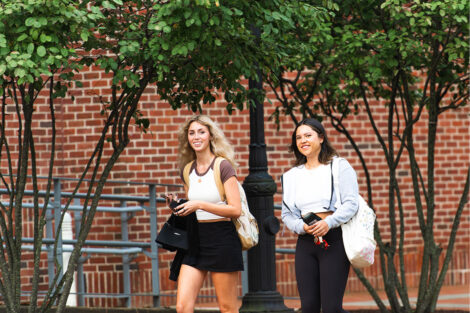 Two students smile as they walk.