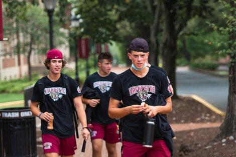 Students, wearing Lafayette College athletics apparel, walk along a brick pathway.