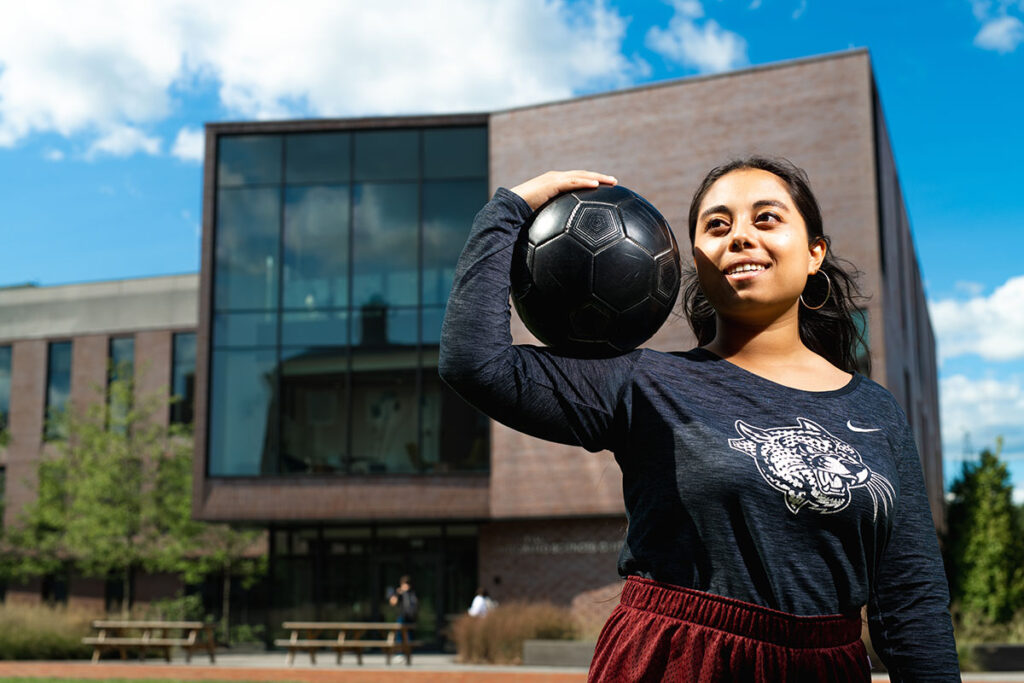 Flor De Maria Caceres Godoy holds a soccer ball outside of Rockwell Integrated Sciences Center