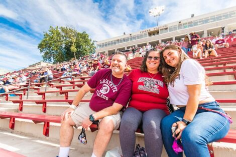 A family watches the football game from the stands of Fisher Stadium.