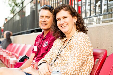 President Nicole Hurd and Bill Hurd sit in the stadium of Fisher Field.