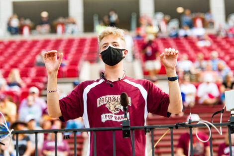 A student conducts the band on Fisher Field.