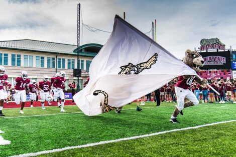 The Lafayette Leopard runs across Fisher Field, carrying a flag with a Leopard on it. Football players run behind.
