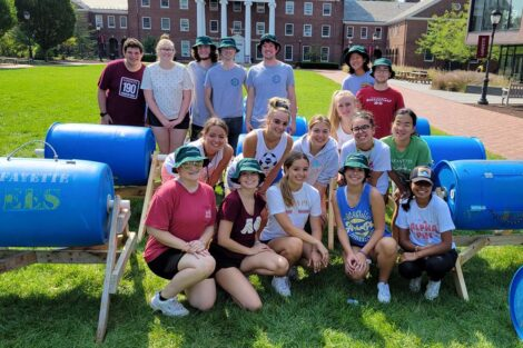 Many new composters surround the students who build them