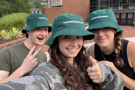 Student volunteers wear Lafarmapalooza hats and flash the peace sign and thumbs up